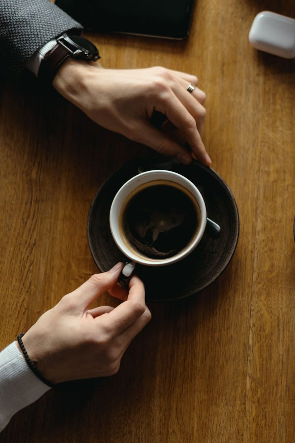 Top view two men hands gesticulating while holding cups of coffee on a wooden table background