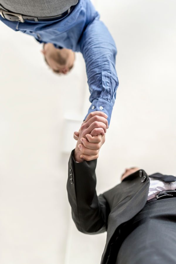 Businessmen shaking hands on a deal or agreement , in welcome or in congratulations, low angle view.